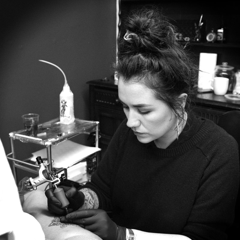 Lauren Shaw tattoo artist profile image whilst tattooing at Heart for Art Tattoo.