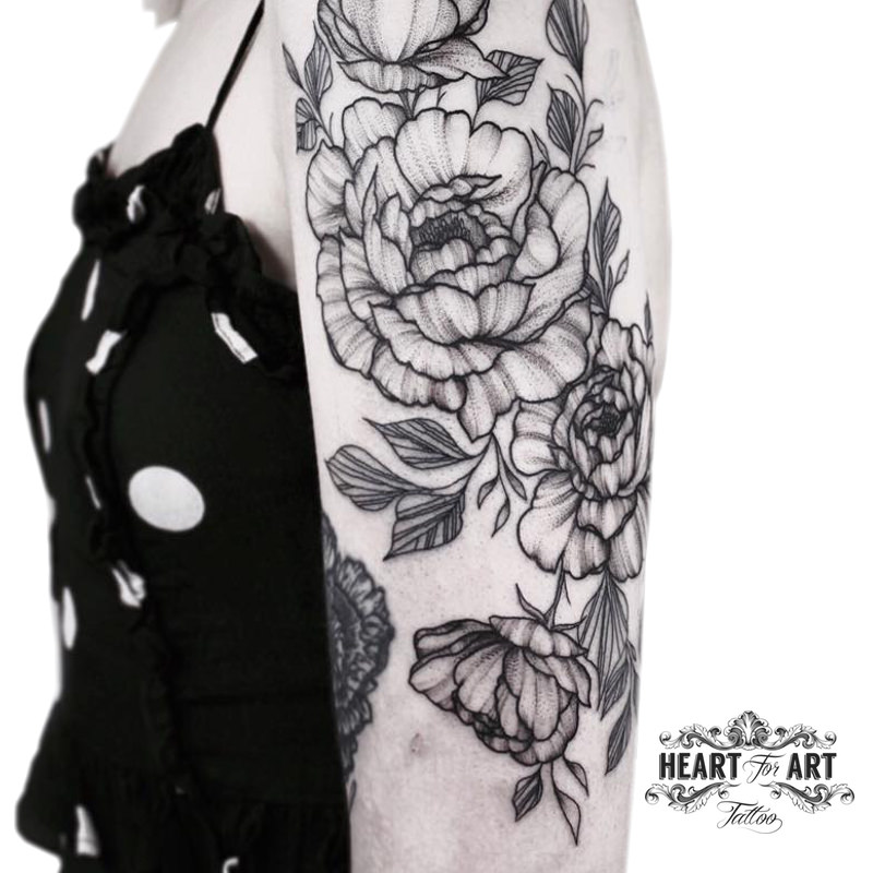 Lady with black top posing for a blackwork and linework flowers tattoo.